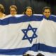 DVI Dancers in Finland, featuring Dr. Kristiina Ramo, Prof. Tapani Ramo, and Yuval Tabashi, choreographer and dance teacher from the Israeli Dance Institute in London. Look at the happy faces of the dancers standing behind the Israeli Flag.